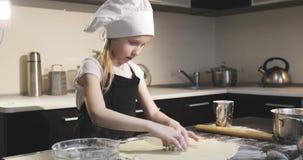 A menina doce em um tampão do avental e do cozinheiro chefe cortou a forma na massa da cookie vídeos de arquivo