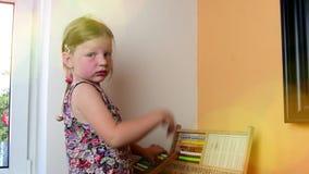 A menina doce joga com ábaco e escreve no quadro-negro com giz Conceito pré-escolar, conceito da infância brinquedo filme