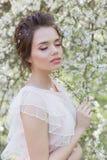 Menina doce macia bonita em um vestido cor-de-rosa com uma árvore de florescência próxima do penteado em um dia de mola ensolarad Fotografia de Stock