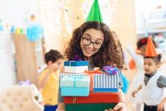 A menina doce no chapéu festivo verde exulta no grande número de presentes no aniversário Festa de anos feliz Imagens de Stock