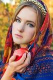Menina doce nova bonita em um lenço com a borda na cabeça com Apple vermelho em sua mão, como um caráter do conto de fadas Imagem de Stock Royalty Free