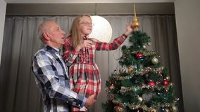 Menina doce que ajusta a parte superior da árvore de Natal filme