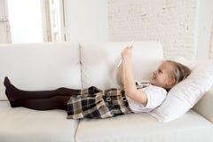 Menina doce que encontra-se no sofá home do sofá usando o Internet app na almofada digital da tabuleta Fotos de Stock Royalty Free
