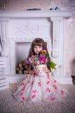 Menina doce que senta-se com um grupo de flores Fotos de Stock Royalty Free