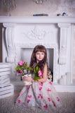 Menina doce que senta-se com um grupo de flores Fotos de Stock