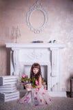 Menina doce que senta-se com um grupo de flores Foto de Stock Royalty Free