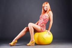 Menina doce que senta-se na esfera Fotografia de Stock Royalty Free