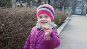 Menina doce que sorri e que guarda uma planta pequena em suas mãos video estoque
