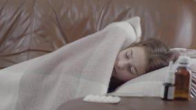 Menina doente adolescente que encontra-se no sofá coberto com uma cobertura em casa, está fria Pulverizador nasal, comprimidos e  filme