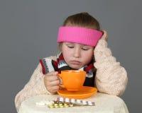 A menina doente bebe o chá imagem de stock