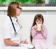 A menina doente bebe o chá quente que senta-se perto do doutor Fotografia de Stock Royalty Free