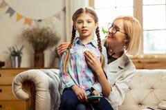 Menina doente bonito que senta-se nos joelhos do pediatra de incandescência fotografia de stock