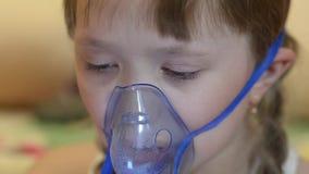 A menina doente na máscara para a inalação, menina no hospital é tratada pela inalação video estoque