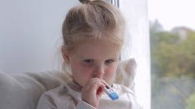 A menina doente nova mede a temperatura perto da janela Guardando o termômetro em sua boca vídeos de arquivo