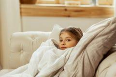 Menina doente pequena com um frio que encontra-se na cama fotografia de stock royalty free