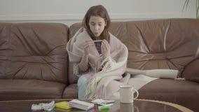 Menina doente pequena do retrato para sentar-se no sofá, nas tabuletas, nos comprimidos e no copo na tabela Termômetro de vista f filme