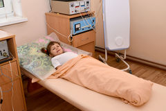 A menina doente pequena encontra-se em um sofá em um offi fisioterápico Fotografia de Stock