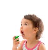 A menina doente pequena usou o pulverizador médico para a respiração isolada Foto de Stock