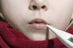 Menina doente que encontra-se na cama com um termômetro na boca Fotos de Stock Royalty Free