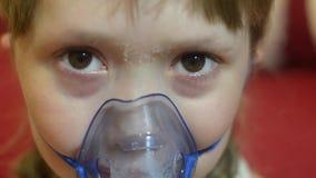 A menina doente que sorri na máscara para a inalação, menina no hospital é tratada pela inalação filme