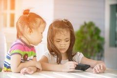 Menina dois asiática pequena que senta-se na cadeira usando o telefone celular Fotos de Stock