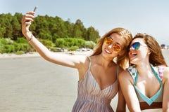 Menina dois atrativa que está junto, levantando e fazendo a praia do selfie Imagem de Stock Royalty Free