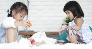 Menina dois bonito asiática pequena que joga o bloco de madeira colorido na cama junto vídeos de arquivo