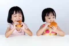 Menina dois chinesa asiática que come o hamburguer Fotos de Stock Royalty Free