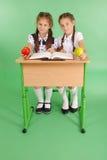 Menina dois em uma farda da escola que senta-se em uma mesa e que lê um livro Imagem de Stock Royalty Free