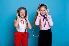 A menina dois escuta a música com fones de ouvido e dança imagens de stock royalty free