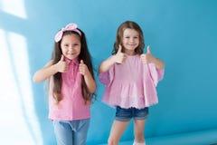 A menina dois mostra o polegar do símbolo das mãos acima fotos de stock royalty free