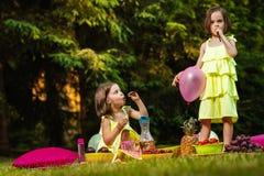 A menina dois nos vestidos está jogando no piquenique Foto de Stock Royalty Free