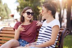 A menina dois tem a conversação amigável no parque, discute algo ativamente, veste óculos de sol na moda, levanta no banco de mad foto de stock