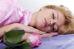 A menina dorme com uma rosa Fotografia de Stock Royalty Free