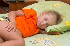 A menina dorme em seu lado em sua mão sob o descanso da cama Fotografia de Stock Royalty Free