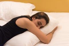 A menina dorme em sua cama imagens de stock royalty free