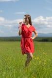 menina dos anos de idade 20 no vestido vermelho que aspira uma flor amarela Fotografia de Stock Royalty Free