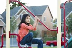 Menina dos anos de idade nove que joga no campo de jogos Fotos de Stock