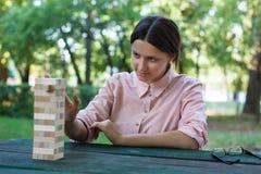A menina dos concentrados está jogando em um jogo de madeira do bloco Imagens de Stock Royalty Free