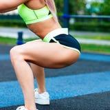 Menina dos esportes no sportswear que squatting no parque do verão foto de stock royalty free