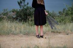 Menina dos pés em um vestido preto com ramalhete Imagem de Stock Royalty Free