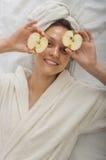 Menina dos termas que guarda duas metades das caras em torno da maçã Fotos de Stock Royalty Free