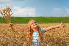 Menina dourada do cabelo no campo de trigo Fotografia de Stock
