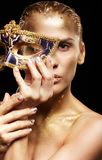 Menina dourada no fundo preto Fêmea com o disfarce venecian Imagens de Stock
