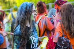 A menina drapejou no pó azul na corrida da cor foto de stock