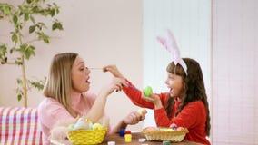 A menina durante o treinamento com Páscoa feliz toca no nariz da sua mãe a filha começa a rir lá, e na tabela video estoque
