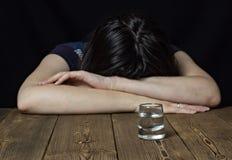 Menina e álcool bêbados em um fundo de madeira, alianças de casamento em uma tabela, união do divórcio fotos de stock royalty free