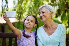 Menina e avó de sorriso que tomam o selfie Fotos de Stock