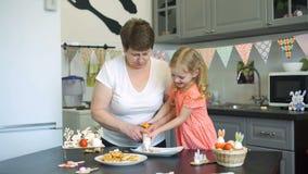 Menina e avó que têm o divertimento ao cozinhar video estoque
