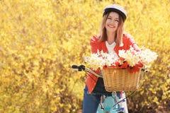 Menina e bicicleta bonitas novas com as flores na cesta Foto de Stock